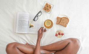 erson Holding White Ceramic Mug With Lemon Near Book and Sliced Bread on White Comforter